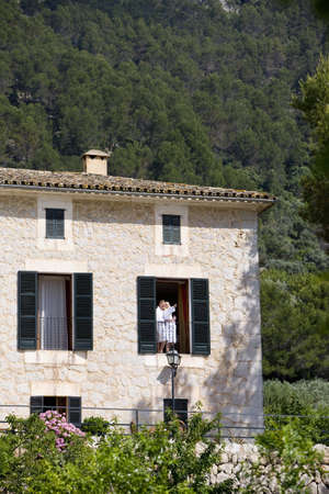 m hotel: Couple in bathrobes standing on sunny manor balcony