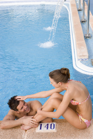 ruffling: Woman ruffling manÕs hair at edge of swimming pool LANG_EVOIMAGES