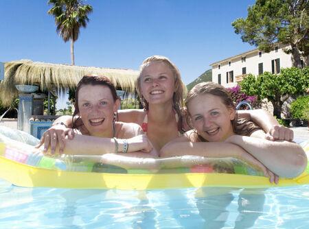 Portrait of happy teenage girls leaning on pool raft in swimming pool
