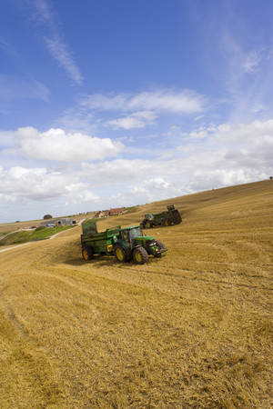 peo: Tractors spreading fertilizer in sunny rural field LANG_EVOIMAGES