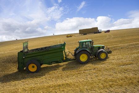 muck: Tractor spreading fertilizer in sunny rural field