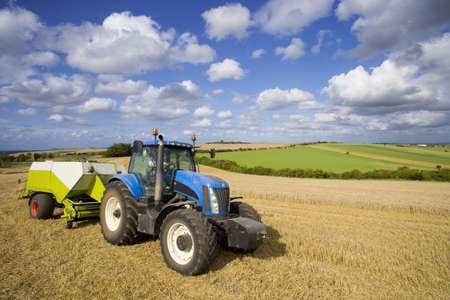 baler: Tractor and baler baling straw in sunny rural field