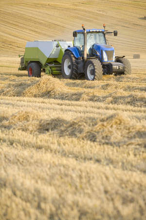 baler: Tractor and straw baler in rural field