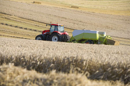 baler: Tractor and straw baler in sunny, rural field LANG_EVOIMAGES