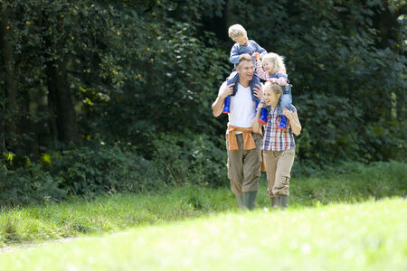 peo: Smiling family walking together outdoors