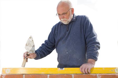 Senior bricklayer with level checking brickwork