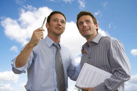 Businessmen working together against blue sky Imagens