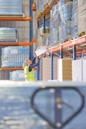 refle: Female warehouse worker lifting box from shelf LANG_EVOIMAGES