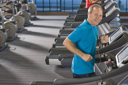 Portrait of smiling man listening to music on headphones and running on treadmill in health club