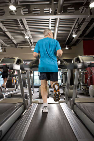 health club: Man running on treadmill in health club