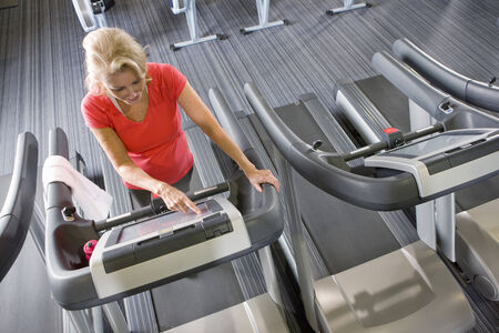 health club: Senior woman programming treadmill in health club