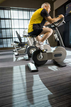 health club: Man riding exercise bike in health club