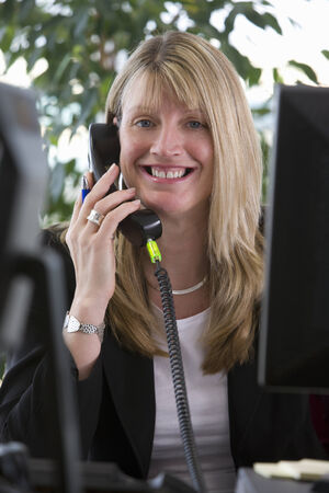 peo: Smiling businesswoman talking on telephone at desk LANG_EVOIMAGES