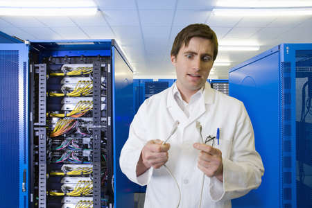 Confused IT technician looking at LAN cable in network server room Stock Photo