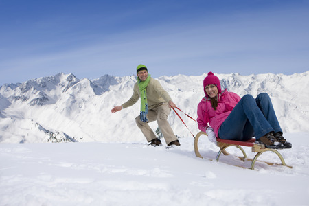 leis: Man pulling woman up ski slope on sled LANG_EVOIMAGES