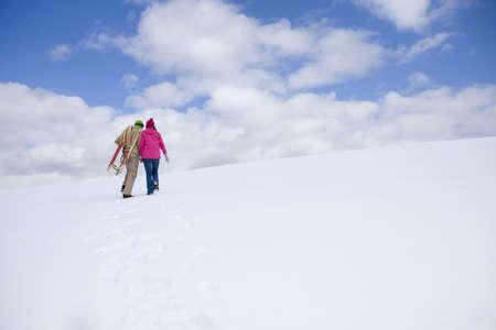 ski walking: Couple walking up ski slope carrying sled
