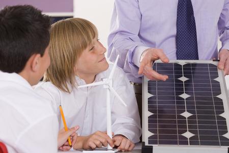 enviro: Students listening to teacher explaining solar panel and wind turbines in classroom