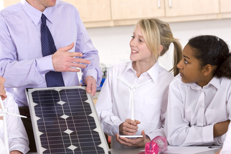 carbon neutral: Students listening to teacher explaining solar panel and wind turbines in classroom
