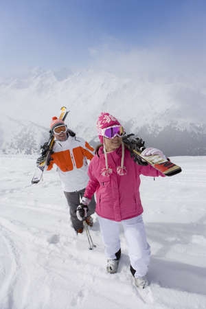 leis: Skiers carrying skis across ski slope LANG_EVOIMAGES