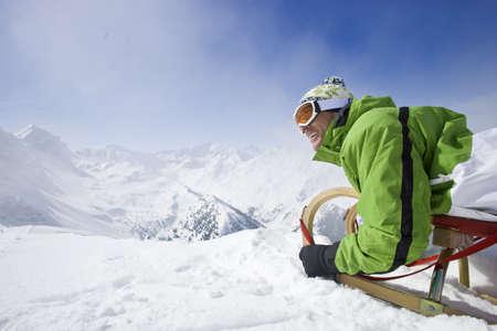 cima montagna: Uomo sorridente con la slitta in cima della montagna
