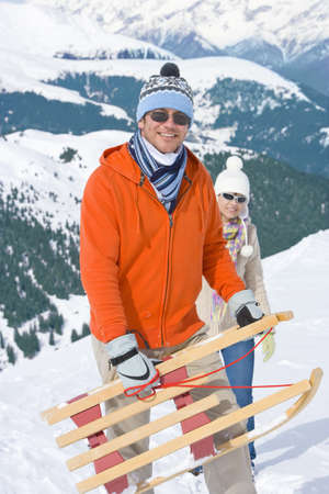 mountaintops: Couple standing in hillside together holding sled