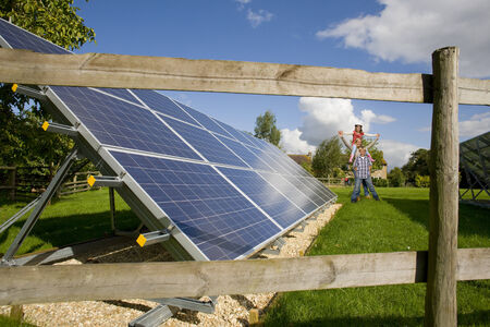 carbon neutral: Happy family standing near large solar panels