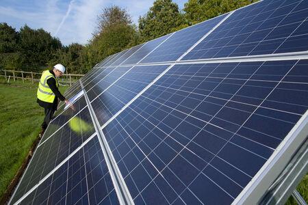 carbon neutral: Technician with blueprints standing near large solar panels