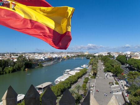 plaza of arms: Spanish flag fluttering with city and river in background,Seville,Spain
