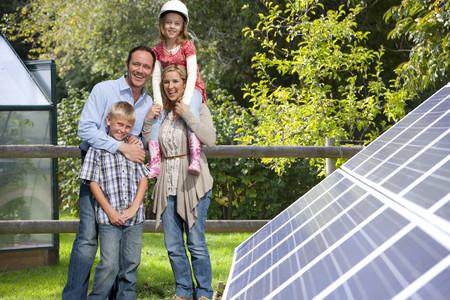 대형 태양 전지 패널 근처의 행복한 가족 서 스톡 콘텐츠