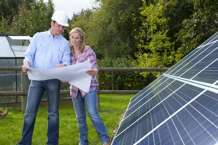 carbon neutral: Technicians holding blueprints talking near large solar panels