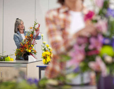 evening class: Smiling woman putting flowers into floral arrangement in classroom LANG_EVOIMAGES