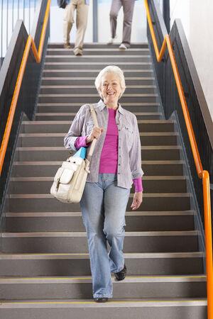down the stairs: Estudiantes adultos caminando por las escaleras en la universidad para llegar a clases nocturnas LANG_EVOIMAGES