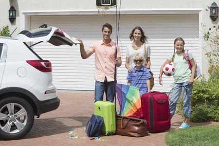 chobot: Portrét usmívající se rodinné balení auto slunné příjezdové cestě