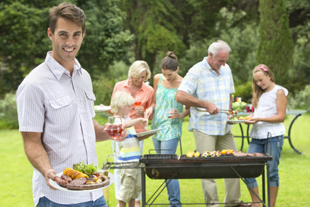 meat lover: Portrait of smiling man with plate of barbecue and wine glass with family in background LANG_EVOIMAGES