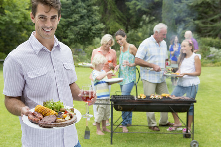 Portrait of smiling man holding plate of barbecue and glass of wine with family in background