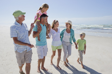 father and son holding hands: Multi-generation family walking on sunny beach LANG_EVOIMAGES