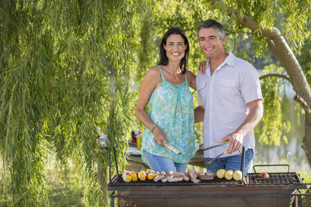 grill tongs sausage: Couple Cooking Barbeque In Countryside