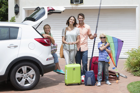 Portrait of smiling family packing car in sunny driveway Stock Photo