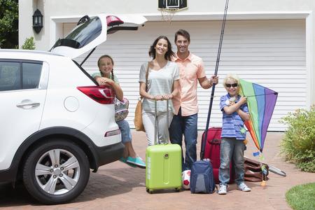 girl sport: Ritratto di sorridere auto imballaggio di famiglia in viale pieno di sole LANG_EVOIMAGES