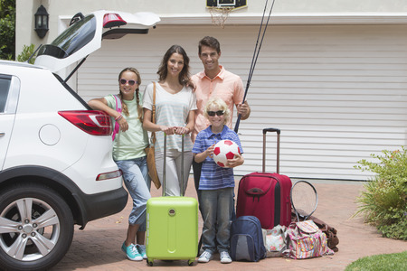 Portrait of smiling family packing car in sunny driveway Imagens