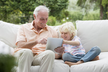 silver surfer: Grandfather and grandson using digital tablet on outdoor sofa