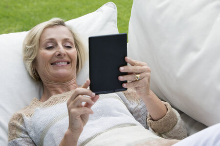 silver surfer: Senior woman laying on outdoor sofa and using digital tablet
