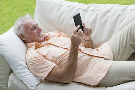 silver surfer: Senior man laying on outdoor sofa and using digital tablet