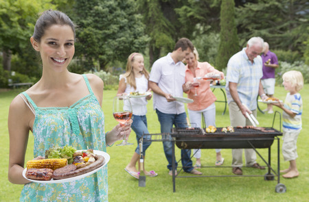 meat lover: Portrait of smiling woman holding plate of barbecue and glass of wine with family in background