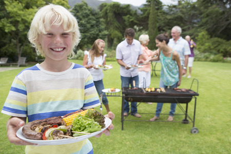 meat lover: Portrait of smiling boy holding plate of barbecue with family in background