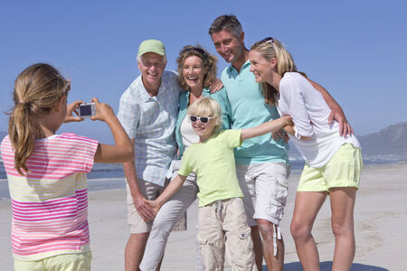 getting away from it all: Girl with digital camera photographing multi-generation family on sunny beach