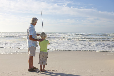 grandfather: Abuelo y nieto con ca�a de pescar en la playa asoleada