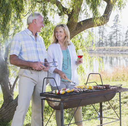 grill tongs sausage: Senior Couple Cooking Barbeque In Countryside LANG_EVOIMAGES