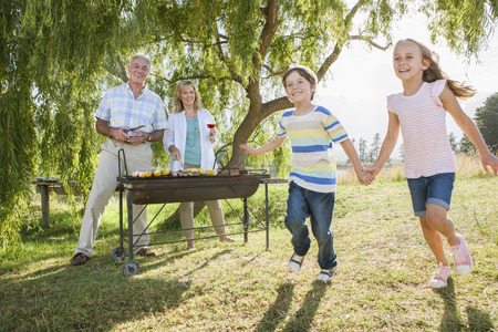 grill tongs sausage: Grandparents Serving Grandchildren At Family Barbeque