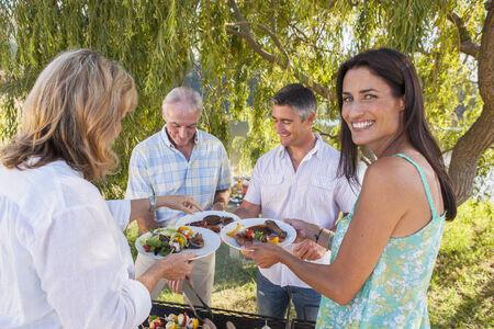 Erwachsene Familiengruppe Kochen Barbeque in Landschaft